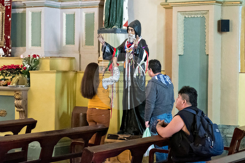 Worshippers stop to tie ribbons to a saint inside the Basílica Colegiata de Nuestra Señora de Guanajuato or Guanajuato Basilica in the historic center of Guanajuato City, Guanajuato, Mexico. The massive basilica was built in 1671 and contains a jewel incrusted image of the Virgin Mary.