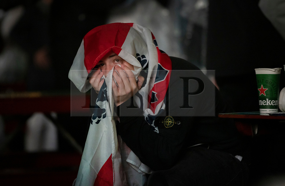 © Licensed to London News Pictures. 11/07/2021. London, UK. A supporter sits wrapped in a flag at the Trafalgar Square fan zone after watching England lose to Italy during the EURO 2020 final. Photo credit: Peter Macdiarmid/LNP