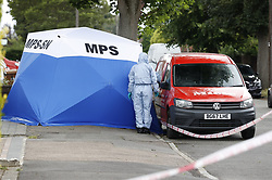 © Licensed to London News Pictures. 19/06/2020. London, UK. Forensics officers work at the crime scene in North Cheam after a fatal shooting. Police were called at 01:12hrs on Friday, 19 June to reports of shots fired on Brocks Drive in North Cheam. Officers, including firearms officers, attended, and found a man, believed to be in his mid-20s, in the street suffering from a gunshot injury. They immediately provided first aid. The London Ambulance Service and London's Air Ambulance also attended but despite the efforts of officers and paramedics, the man was pronounced dead at the scene at 01:45hrs. Photo credit: Peter Macdiarmid/LNP