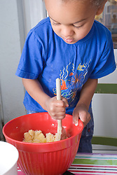 Little boy stirring a mixing bowl as he makes a cake,