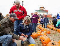 Jerry Vermette shields the wind for his wife Claire as they begin to light pumpkins in downtown Laconia during Pumpkin Fest on Saturday.  (Karen Bobotas/for the Laconia Daily Sun)