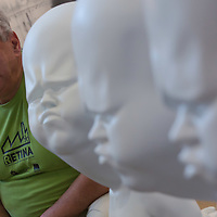 Visitor imitates the facial expression of a set of sculptures by Viktor Freso on display at Art Market exhibition in Budapest, Hungary on October 12, 2014. ATTILA VOLGYI