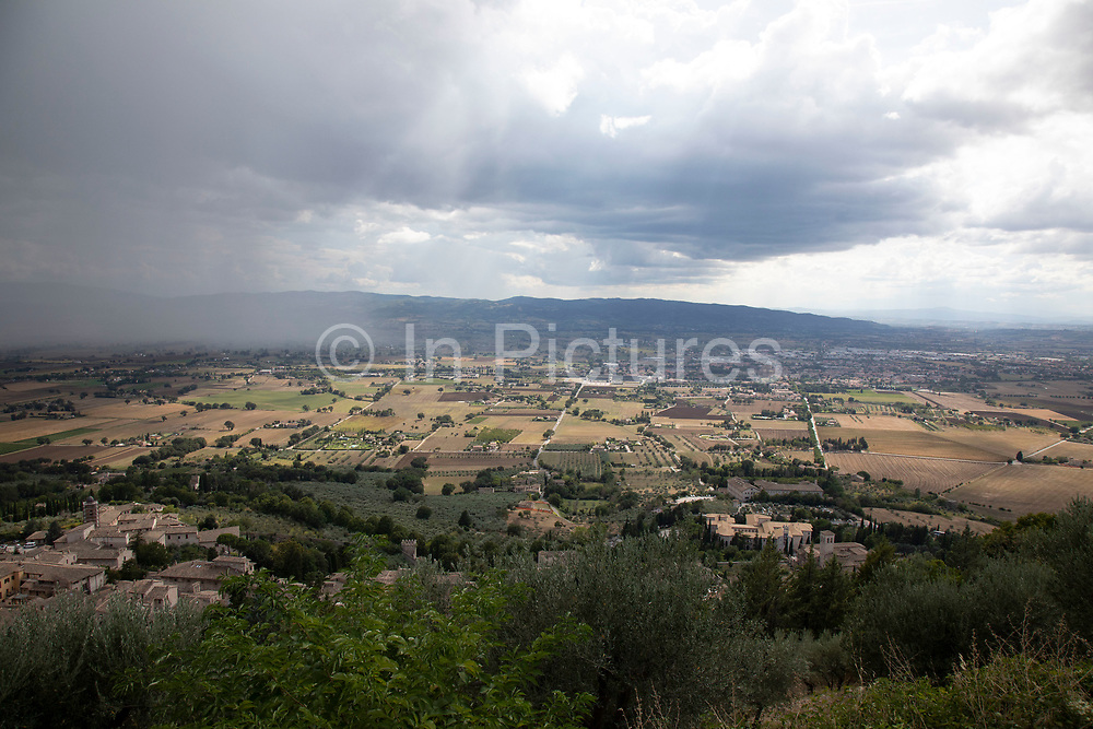 View over the valley as rain falls south of Assisi, Umbria, Italy. Assisi is a town in the Province of Perugia in the Umbria region, on the western flank of Monte Subasio. It is generally regarded as the birthplace of the Latin poet Propertius, and is the birthplace of St. Francis, who founded the Franciscan religious order in the town in 1208, and St. Clare, Chiara dOffreducci, the founder of the Poor Sisters, which later became the Order of Poor Clares after her death. Assisi is now a major tourist destination for those sightseeing or for more religious reasons.