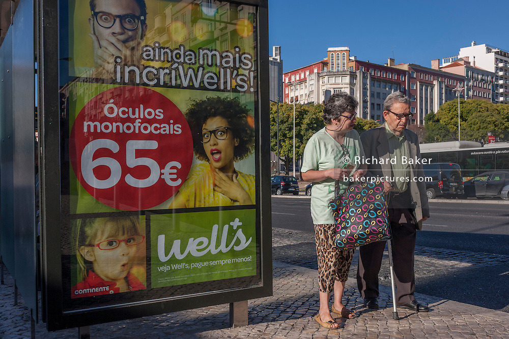 An elderly couple walk slowly past an advert for spectacles (oculos) from the Portuguese retailer Well's, on 14th July 2016, in Lisbon, Portugal. The street is busy with rush hour traffic at Alameda underground Metro station and the wife helps her inform husband to walk with the aide of a stick. (Photo by Richard Baker / In Pictures via Getty Images)