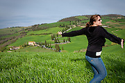 A woman twirls with joy in a green meadow above a winding highway, near Montichiello in the Val d'Orcia region of Tuscany, Italy.
