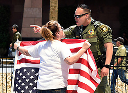 April 15, 2017 - Las Vegas, Nevada, U.S. - COLLEEN BROLA (L) of Henderson, Nevada argues with a Las Vegas police officer during a Tax Day protest at the Trump International Tower.  Activists in cities across the nation are marching today to call on President Donald Trump to release his tax returns. (Credit Image: © David Becker via ZUMA Wire)