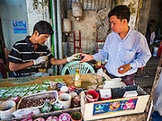 "06 NOVEMBER 2015 - YANGON, MYANMAR: A man buys betel nut from a vendor on a Yangon street. Some economists think Myanmar's informal economy is larger than the formal economy. Many people are self employed in cash only businesses like street food, occasional labor and day work, selling betel, or working out of portable street stalls, doing things like luggage repair. Despite reforms in Myanmar and the expansion of the economy, most people live on the informal economy. During a press conference this week, Burmese opposition leader Aung San Suu Kyi said, ""a great majority of our people remain as poor as ever.""  PHOTO BY JACK KURTZ"