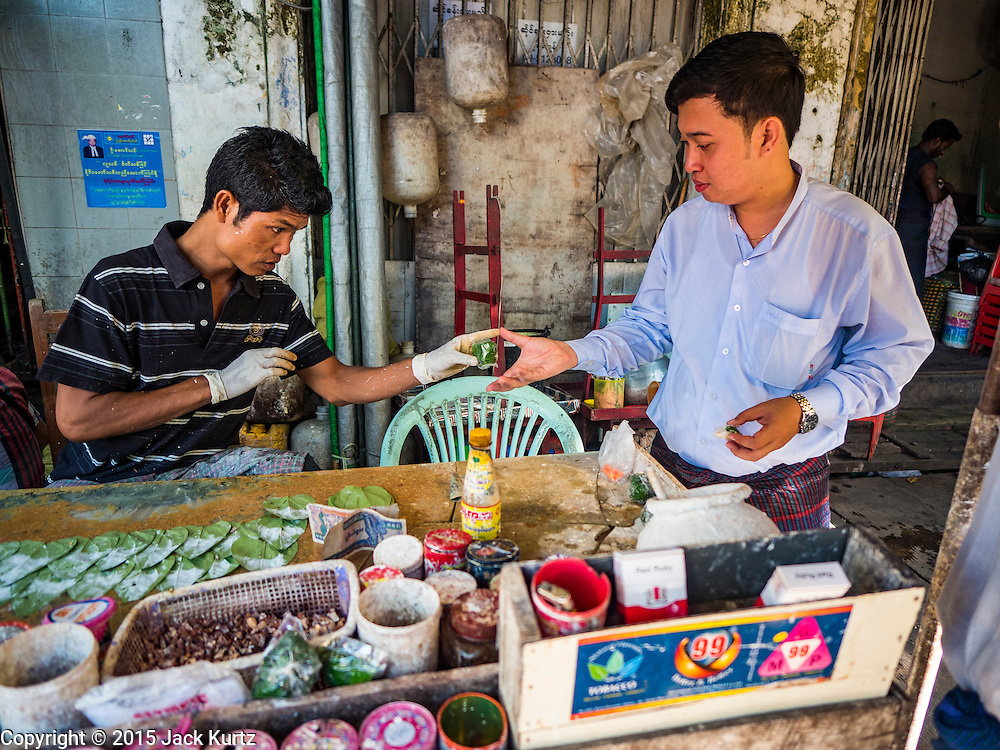 """06 NOVEMBER 2015 - YANGON, MYANMAR: A man buys betel nut from a vendor on a Yangon street. Some economists think Myanmar's informal economy is larger than the formal economy. Many people are self employed in cash only businesses like street food, occasional labor and day work, selling betel, or working out of portable street stalls, doing things like luggage repair. Despite reforms in Myanmar and the expansion of the economy, most people live on the informal economy. During a press conference this week, Burmese opposition leader Aung San Suu Kyi said, """"a great majority of our people remain as poor as ever.""""  PHOTO BY JACK KURTZ"""