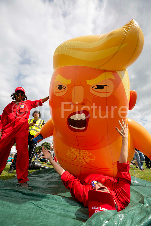 The Trump Baby sitting team dressed in red boiler suits deflate the six metre high inflatable TrumpBaby balloon for the demo on the Meadows in Edinburgh for the Scottish demonstration. United Kingdom. 14th July 2018.