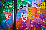 """SHOT 2/8/20 10:36:06 AM - Hand painted heart shaped signs of amor and love hang in front of papel picado banners decorating a side street in Sayulita, Mexico. Papel picado (""""perforated paper,"""" """"pecked paper"""") is a decorative craft made by cutting elaborate designs into sheets of tissue paper and is considered a Mexican folk art. Papel picados are commonly displayed for both secular and religious occasions, such as Easter, Christmas, the Day of the Dead, as well as during weddings, quinceañeras, baptisms, and christenings. Sayulita is a small fishing village about 25 miles north of downtown Puerto Vallarta in the state of Nayarit, Mexico, with a population of approximately 4,000. Known for its consistent river mouth surf break, roving surfers """"discovered"""" Sayulita in the late 60's with the construction of Mexican Highway 200. In recent years, it has become increasingly popular as a holiday and vacation destination, especially with surfing enthusiasts and American and Canadian tourists. (Photo by Marc Piscotty / © 2020)"""