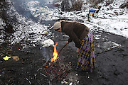 Roma woman recycling worker, burning away plastic and rubber from electric cables, to sell the metal. Roma squat in the snow in one of the largest Roma encampments 'bidounvilles' outside Paris. Winter, Sarcelles, Paris suburbs, France<br /><br />Eastern european Roma migrants, often from Romania and Bulgaria, searching for better opportunities, they move near to western european cities. They typically are poor and live in squats, here around the periphery of Paris, in the suburbs 'banlieu' where they typically build ramshackle homes from recycled wooden panels and corrugated iron, or sometimes benders made from branches covered in tarpaulins. They live in woods and forest, industrial estates or derelict buildings. Life is especially difficult for them in the harsh conditions of winter and rain. Most of these camps get destroyed by police and Roma are eventually evicted, some deported back home or moving on to build another home. They often survive by recycling metal and electronic goods, selling recycled clothes and objects they find in trash bins, or through begging or playing music on the city streets or inside metro stations. Paris, France