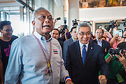 """08 APRIL 2014 - BANGKOK, THAILAND:  SUTHEP THAUGSUBAN (left) and KITTIPONG KITTAYARK, Permanent Secretary of the Thai Ministry of Justice, walk into the Ministry building in Bangkok. Several hundred anti-government protestors led by Suthep Thaugsuban went to the Ministry of Justice in Bangkok Tuesday. Suthep and the protestors met with representatives of the Ministry of Justice and expressed their belief that Thai politics need to be reformed and that corruption needed to be """"seriously tackled."""" The protestors returned to their main protest site in Lumpini Park in central Bangkok after the meeting.   PHOTO BY JACK KURTZ"""