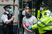 Metropolitan Police officers arrest an activist from HS2 Rebellion, an umbrella campaign group comprising longstanding campaigners against the HS2 high-speed rail link as well as Extinction Rebellion activists, who had glued himself to the doors of the Department for Transport during a protest on 4 September 2020 in London, United Kingdom. Activists glued themselves to the doors and pavement outside the building and sprayed fake blood around the entrance during a protest which coincided with an announcement by HS2 Ltd that construction of the controversial £106bn high-speed rail link will now commence.