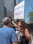 "A woman at the anti-Sharia law in Chicago holds a sign reading ""Unapoligically Muslim"""
