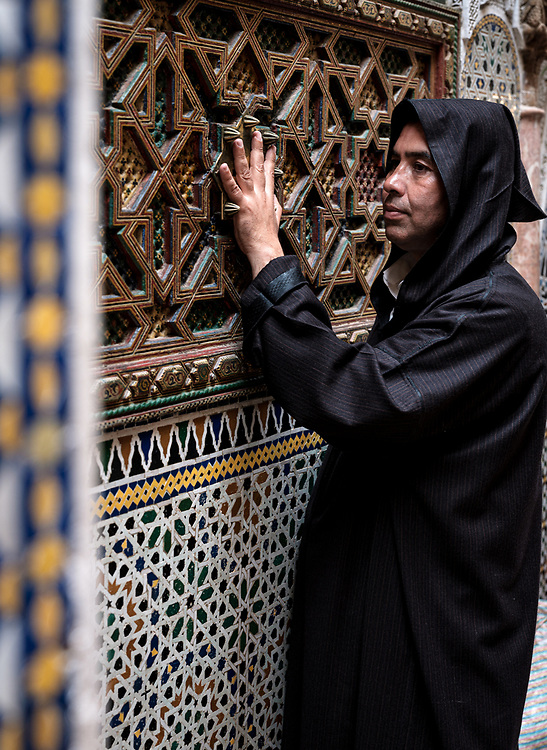 FEZ, MOROCCO - CIRCA MAY 2018:  Moroccan man praying at the courtyard of the Al-Attarine Madrasa in Fez. The courtyard of this small Marinid madrasa is a dazzling example of intricate Islamic architecture.