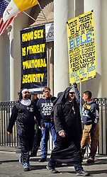 09 February 2016. New Orleans, Louisiana.<br /> Mardi Gras Day. Revelers dressed in habits pass fundamentalist Christians spewing messages of hate outside St Louis Cathedral in the French Quarter. <br /> Photo©; Charlie Varley/varleypix.com