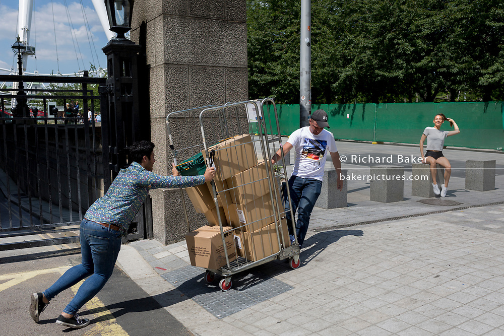 As a young woman poses for photos on the Southbank, deliverymen push a cage of toppling boxes, on 16th July 2019, in London, England. (Part of a larger sequence of 10 images).