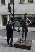 A businessman pauses to the top hat belonging to the statue of 19th century Regency trendsetter, Beau Brummell.