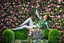 © Licensed to London News Pictures. 25/04/2018. Harrogate UK. Dancer Alison Parson wears a flower dress in front of the flower wall of the Green House display at this years Harrogate Flower Show in which starts tomorrow.  The GREENhouse has been designed to blur the lines between house and garden, creating a home infused with nature complete with living wallpaper,cascading flower shower, an aromatic bed of herbs and even a vege-table. Photo credit: Andrew McCaren/LNP