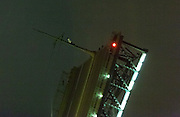 """Man Climbs Bridge as it opens in St Petersburg<br /> <br /> Like any Normal Night St. Petersburg waterfront , security guards slowly puts on the roadway Bridge,. A few minutes later the crowd crawling cries - """" See , the top man! """" a white silhouette wearing a hoodie on its very top. After sitting for ten seconds , he climbs on the pole catenary . And lights fireball And at this time, the young guy hangs upside down on a pole<br /> Guards were outraged but failed to find the guy who successfully disappeared when had enough fun.<br /> <br /> Photo shows; sitting on the catenary pole, the man holds on tight<br /> as the bridge sits upright<br /> ©Exclusivepix"""