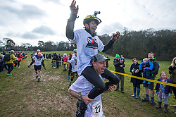 © Licensed to London News Pictures. 06/03/2016. Dorking, UK. Competitors take part in the 2016 Wife Carrying Race in Dorking, Surrey.  The race, which is run over a course of 380m, with both men and women carry a 'wife' over obstacles,  is believed to have originated in the UK over twelve centuries ago when Viking raiders rampaged into the northeast coast of  England carrying off any unwilling local women .  Photo credit: Ben Cawthra/LNP