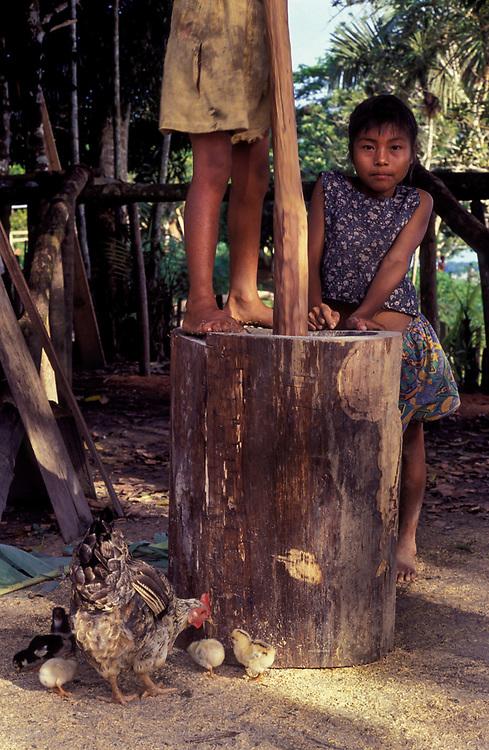 Farmer children grinding maize, near Leticia, Amazonas