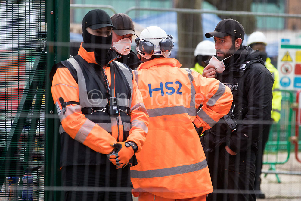 A man wearing a HS2 high-visibility jacket speaks to Karl Harrison c of the National Eviction Team during an operation to remove environmental activists from anti-HS2 campaign group HS2 Rebellion from tunnels beneath Euston Square Gardens on 6th February 2021 in London, United Kingdom. The activists entered tunnels dug by them beneath the site eleven days ago in order to seek to protect trees from felling in connection with the HS2 high-speed rail project.