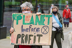 © Licensed to London News Pictures. 30/08/2020. Manchester. A protester holds a placard as she takes part in a protest against colonialism and the financing of fossil fuels. Climate activists from Extinction Rebellion marched through the streets of Manchester. Photo credit: Ioannis Alexopoulos/LNP