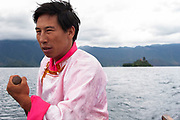 Mo Suo minority man in traditional dress rowing tourists to a nearby island on Lugu Lake, Yunnan, China. Mo Suo are one of approximately 56 different minorities which live in Yunnan, a temperate south eastern province of China in the foothills of the Himalayas.