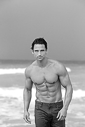 shirtless muscular man in jeans and no shirt in the ocean