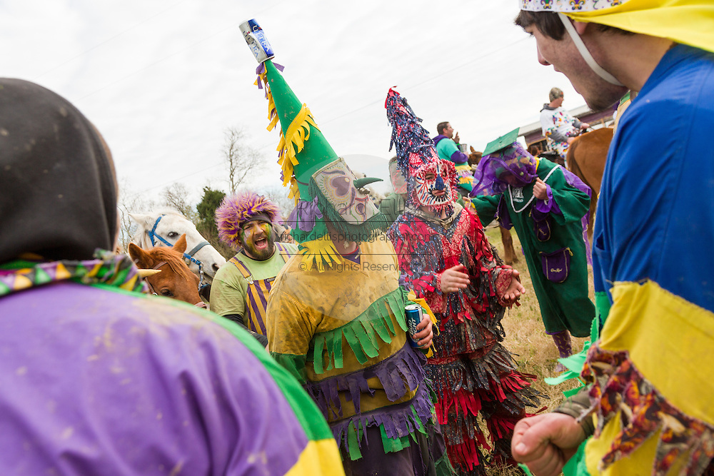 Costumed revelers dance during the Mamou Courir de Mardi Gras chicken run on Fat Tuesday February 17, 2015 in Mamou, Louisiana. The traditional Cajun Mardi Gras involves costumed revelers competing to catch a live chicken as they move from house to house throughout the rural community.