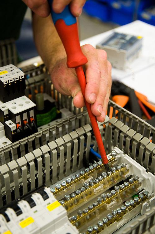 Nederland, Helmond, 26 juni  2009.Electrotechniek. Monteren van draad in een schakelkast. .Foto (c) Michiel Wijnbergh