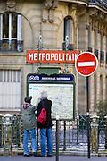 Tourists on foot study Metropolitain subway map for the Paris Metro in Rue du Bac, Left Bank, Paris, France
