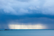 Ominous storm clouds dwarf Portland Harbour as heavy rain pours onto the English Channel beyond, Dorset, England, UK