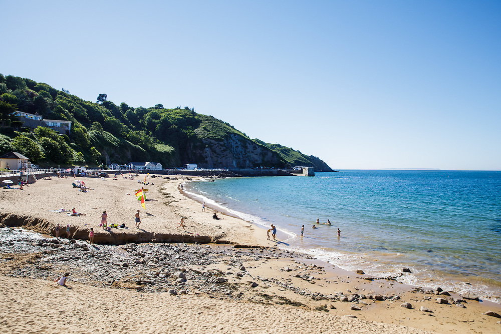 Families and tourists playing on the beach and swimming in the sea at Greve de L'Ecq beach in Jersey, Channel Islands