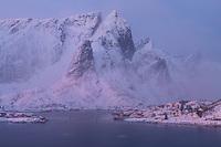 Mountain peaks rise over coastal village of Reine in winter twilight, Moskenesøy, Lofoten Islands, Norway