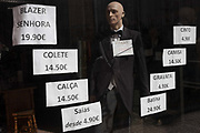 A shop window mannequin advertising prices of varieties of clothing, both academic and less formal styles for men and women, on 19th July, in Porto, Portugal.