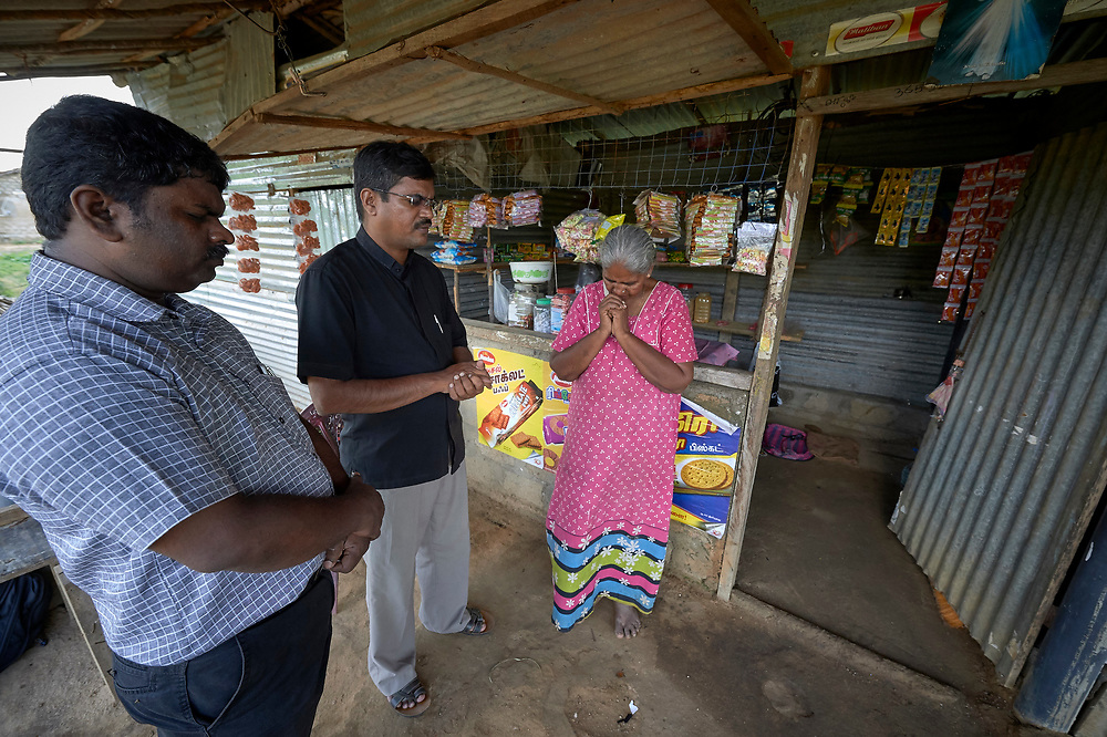 Krishnan Theivanai, who lost her husband and a son during the country's civil war, stands in front of her small shop in Akkarayankulam, Kilinochchi, Sri Lanka, as the Rev. SJ Reginold (left) and the Rev. Thomas Sasikumar pray with her. After the war's end, she participated in a Methodist Church-sponsored women's group, many of whose members were widows whose husbands, like hers, died during the country's brutal civil war. Reginold and Sasikumar are Methodist pastors.