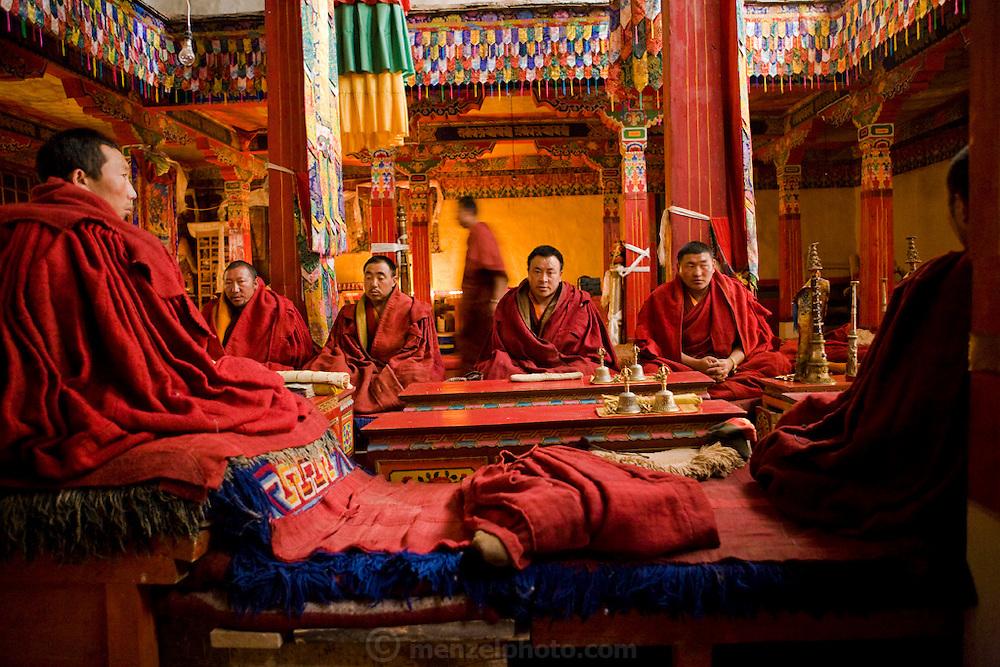 Buddhist monks sit inside a monastery in the Tibetan Plateau.