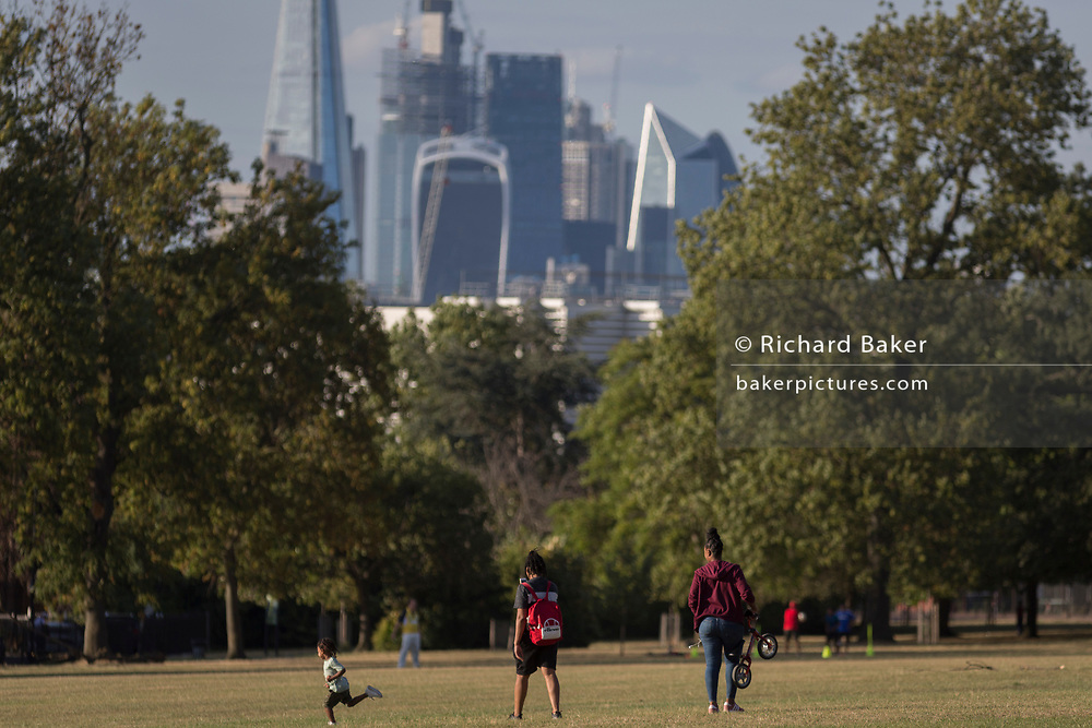 A child runs on grass in Ruskin Park with the skyline of the City of London's financial district, on 8th August 2018, in London, England.