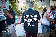 """23 JUNE 2012 - PHOENIX, AZ: A supporter of Sheriff Joe Arapio in front of the Maricopa County Jail in Phoenix Saturday. About 2,000 members of the Unitarian Universalist Church, in Phoenix for their national convention, picketed the entrances to the Maricopa County Jail and """"Tent City"""" Saturday night. They were opposed to the treatment of prisoners in the jail, many of whom are not convicted and are awaiting trial, and Maricopa County Sheriff Joe Arpaio's stand on illegal immigration. The protesters carried candles and sang hymns.      PHOTO BY JACK KURTZ"""