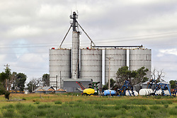 A vintage steel silo sits between the railroad tracks and what appears to be a storage or junk yard in a small community in western Nebraska