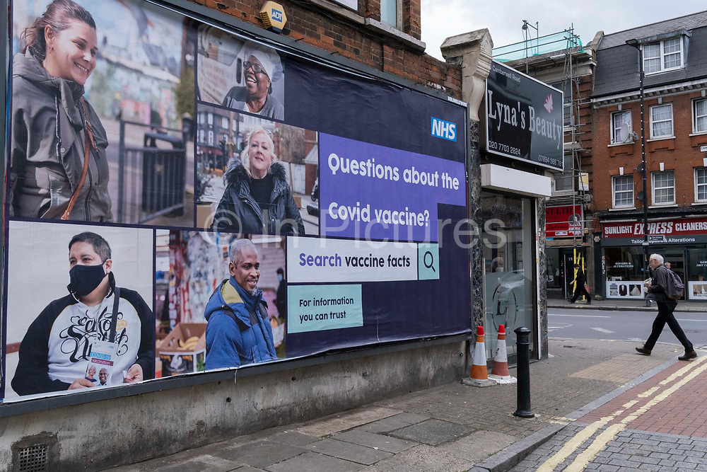 A south Londoner wearing a face covering walks past a governement NHS national Health Service billboard giving a link for official information relating to Covid vaccine facts, an attempt to counter misinformation and conspiracy theories to the public in Lambeth - a borough that has seen high infection rates of Covid and Delta variants, on 6th July 2021, in Camberwell, London, England.