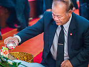 12 OCTOBER 2104 - BANG BUA THONG, NONTHABURI, THAILAND: A man pours scented water over the hand of Apiwan Wiriyachai on the first day of his funeral rites at Wat Bang Phia in Bang Bua Thong, a Bangkok suburb, Sunday. Apiwan was a prominent Red Shirt leader, member of the Pheu Thai Party of former Prime Minister Yingluck Shinawatra, and a member of the Thai parliament. The military government that deposed the elected government in May, 2014, charged Apiwan with Lese Majeste for allegedly insulting the Thai Monarchy. Rather than face the charges, Apiwan fled Thailand to the Philippines. He died of a lung infection in the Philippines on Oct. 6. The military government gave his family permission to bring him back to Thailand for the funeral. He will be cremated later in October. The first day of the funeral rites Sunday drew tens of thousands of Red Shirts and their supporters, in the first Red Shirt gathering since the coup.    PHOTO BY JACK KURTZ