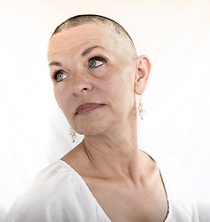 """Donna Branham of Lenore, West Virginia, poses after shaving her head on the steps of the West Virginia Capitol with a group of women in protest to mountaintop-removal mining. The shaving of their heads was symbolic of the mountains that have been stripped of all of the living things on them. It was also symbolic of the many people who are sick or dying as the result of Mountaintop Removal. Mountaintop Removal is a method of surface mining that literally removes the tops of mountains to get to the coal seams beneath. It is the most profitable mining technique available because it is performed quickly, cheaply and comes with hefty economic benefits for the mining companies, most of which are located out of state. It is the most profitable mining technique available because it is performed quickly, cheaply and comes with hefty economic benefits for the mining companies, most of which are located out of state. Many argue that they have brought wage-paying jobs and modern amenities to Appalachia, but others say they have only demolished an estimated 1.4 million acres of forested hills, buried an estimated 2,000 miles of streams, poisoned drinking water, and wiped whole towns from the map. """"People don't know how hard it is on the Appalachian people,"""" Branham said of mountaintop-removal mining. """"They have no idea. And they don't want to know. As long as they don't have to look at it, they can ignore it."""" © Ami Vitale"""