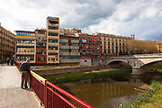 A man looks into the the river Onyar, in Girona, Catalonia, Spain