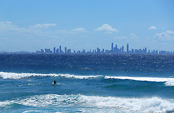 A general view of a surfer in the sea at the Surfers Paradise resort on the Gold Coast, Australia.