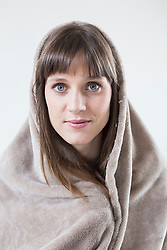 Portrait of mid adult woman covered with blanket, close up