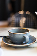 A cup of coffee and a saucer in a coffee shop in England