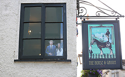 A cutout of Harry and Meghan peering out through a top window in a pub in Windsor of Prince Harry and fiancee Meghan Markle ahead the royal wedding on May 19.